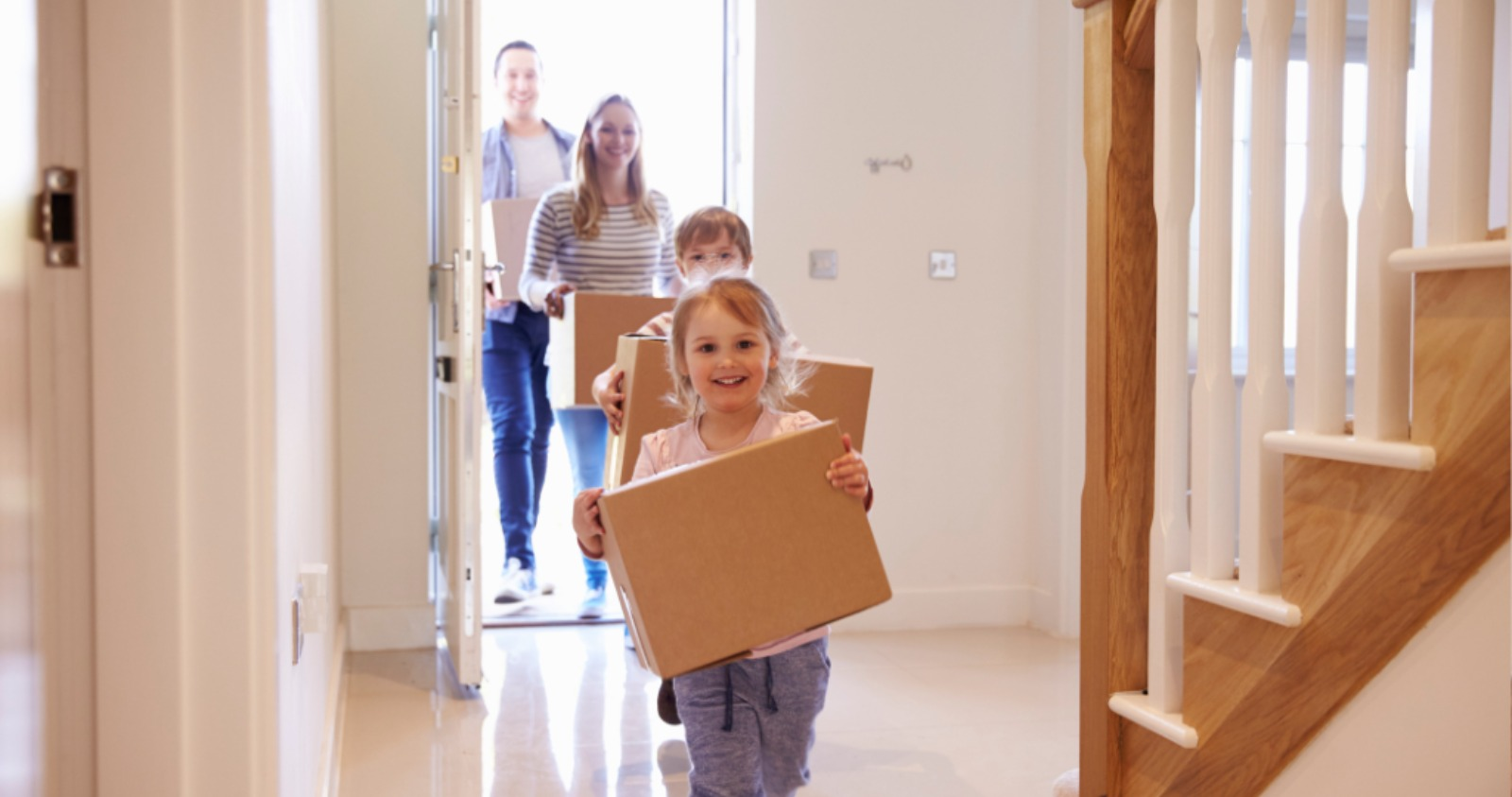family-carrying-boxes-into-new-home-on-moving-day-picture-id546201764